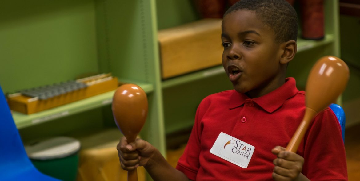 Boy in a red shirt playing two brown maracas
