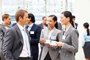 Individuals wearing business suits and name tags standing having a conversation. The focus of the picture is two females, drinking from a coffee mug, talking with a male.
