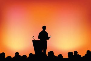 A silhouette of a presenter at a podium and an audience with an orange, yellow, and pink mixture background.