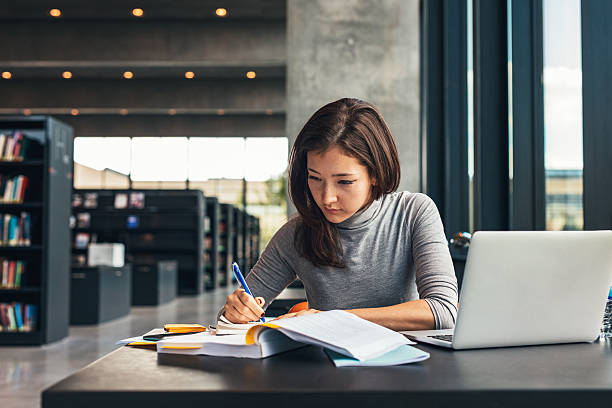 A women sitting at a table with a book opened taking notes while studying.