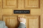 "A man in a grey suit jacket with a white button up knocking on a wooden door with a sign on it that reads, ""opportunity."""