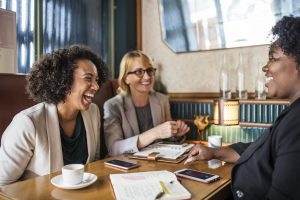 A group of women sitting around a table drinking coffee planning something while smiling and laughing.