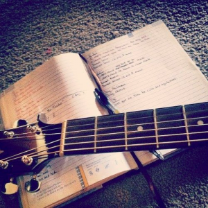 A songwriting book sitting on the floor with the neck of the guitar laying across it.