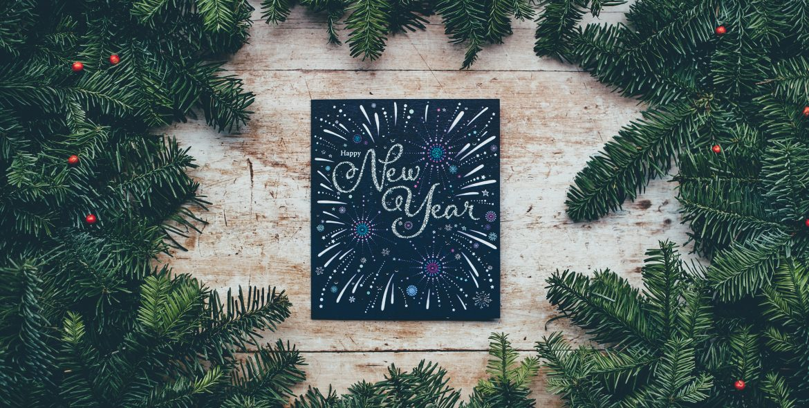 """Greengages garland sprinkled with red berries sitting on a wooden table in a circle. In the middle there is a small black sign that reads, """"New Year,"""" with white, blue, and purple painted fireworks."""