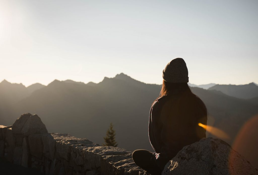 An individual sitting on a mountain top looking at a mountain top view