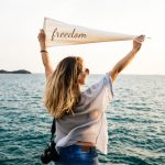 "Women standing on the shore facing a body of water hold a pennant that reads, ""freedom."""