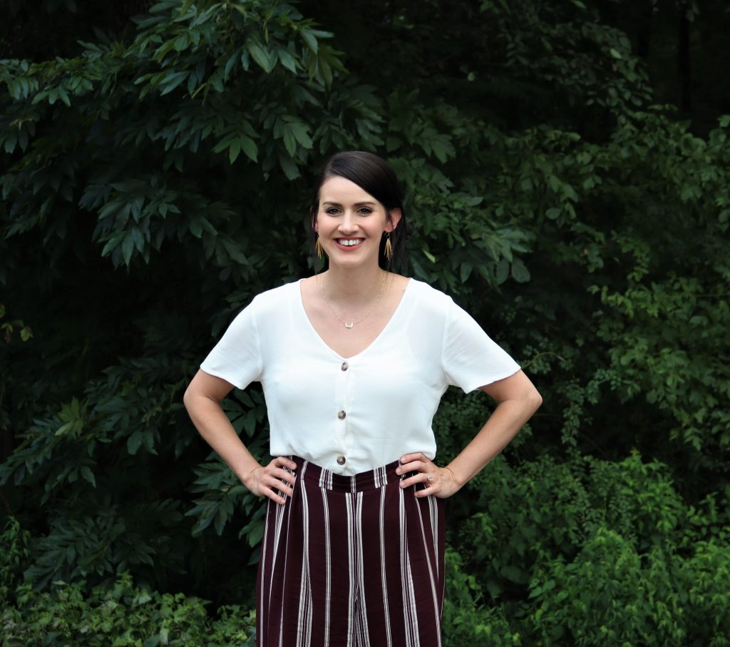 Amy wearing a white shirt with maroon and white striped pants standing in front of a wooded area.
