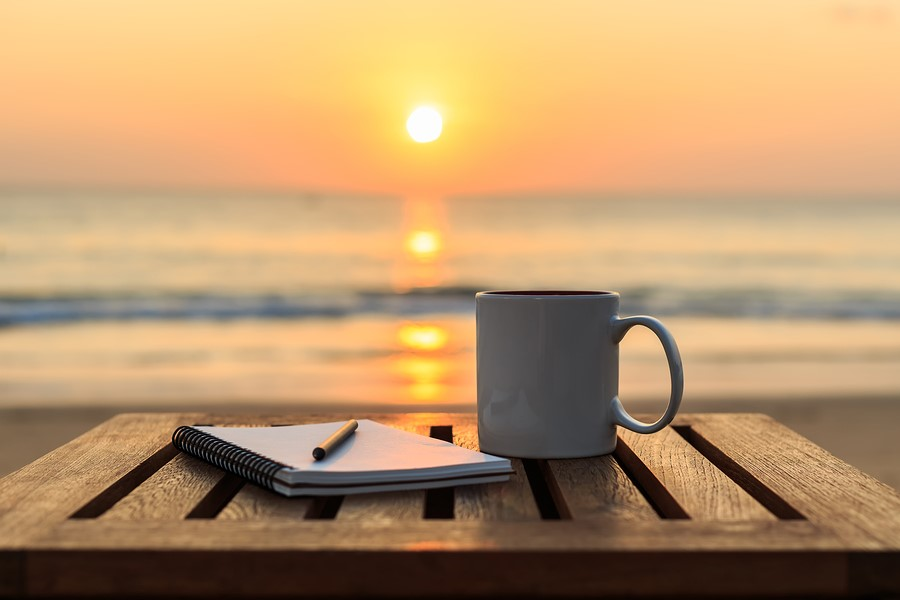 View of wooden table at a beach with sunset over the water in the background, one calm wave. Pencil on white notebook with white mug next to it on table.