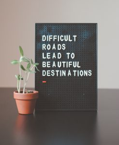 "A letter board sitting on a table top that reads ""difficult roads lead to beautiful destinations,"" with a small plant places beside it."