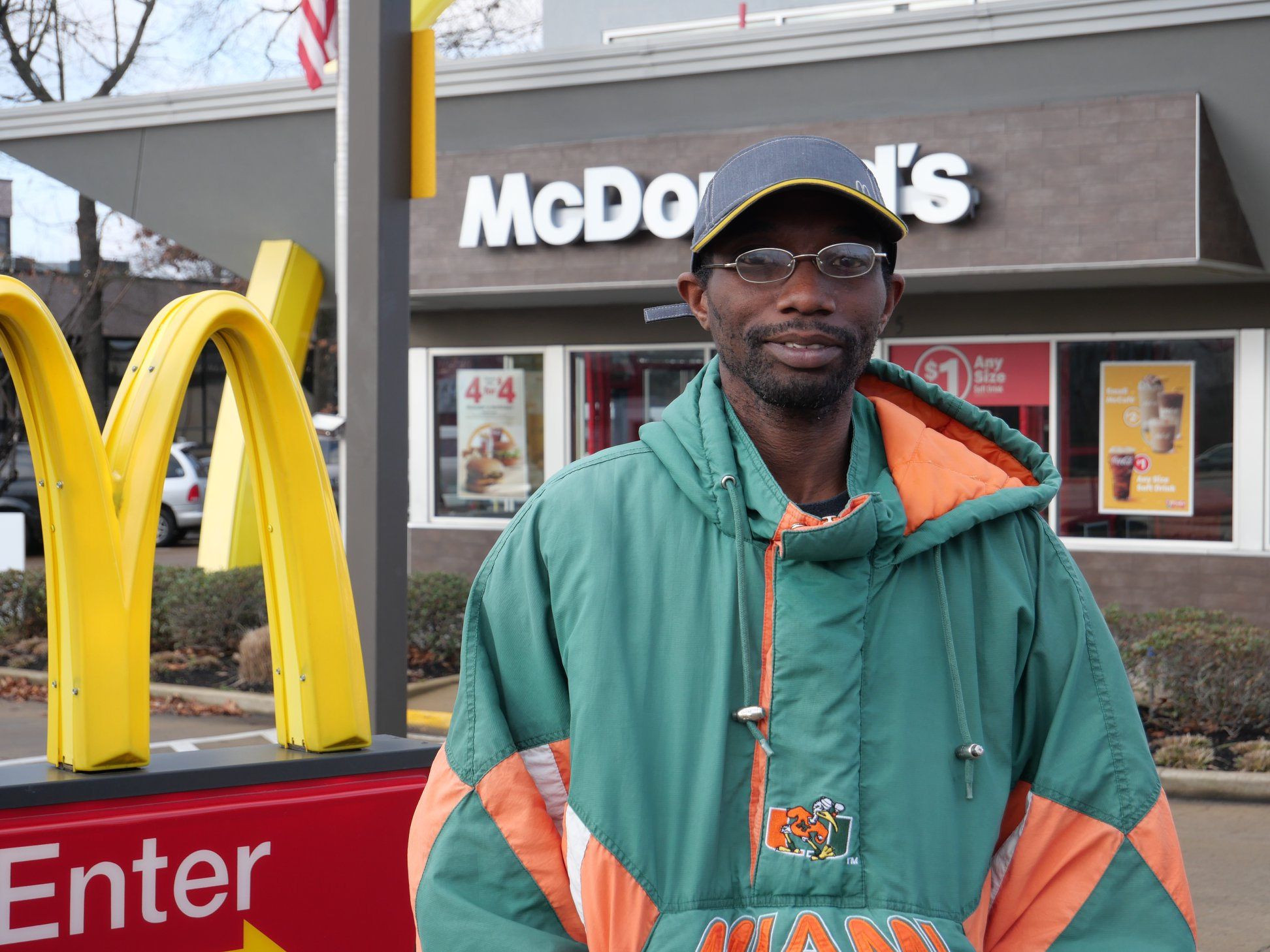 Disabilities should not prevent employment. A photo of Travis, smiling in front of his employer, McDonald's.