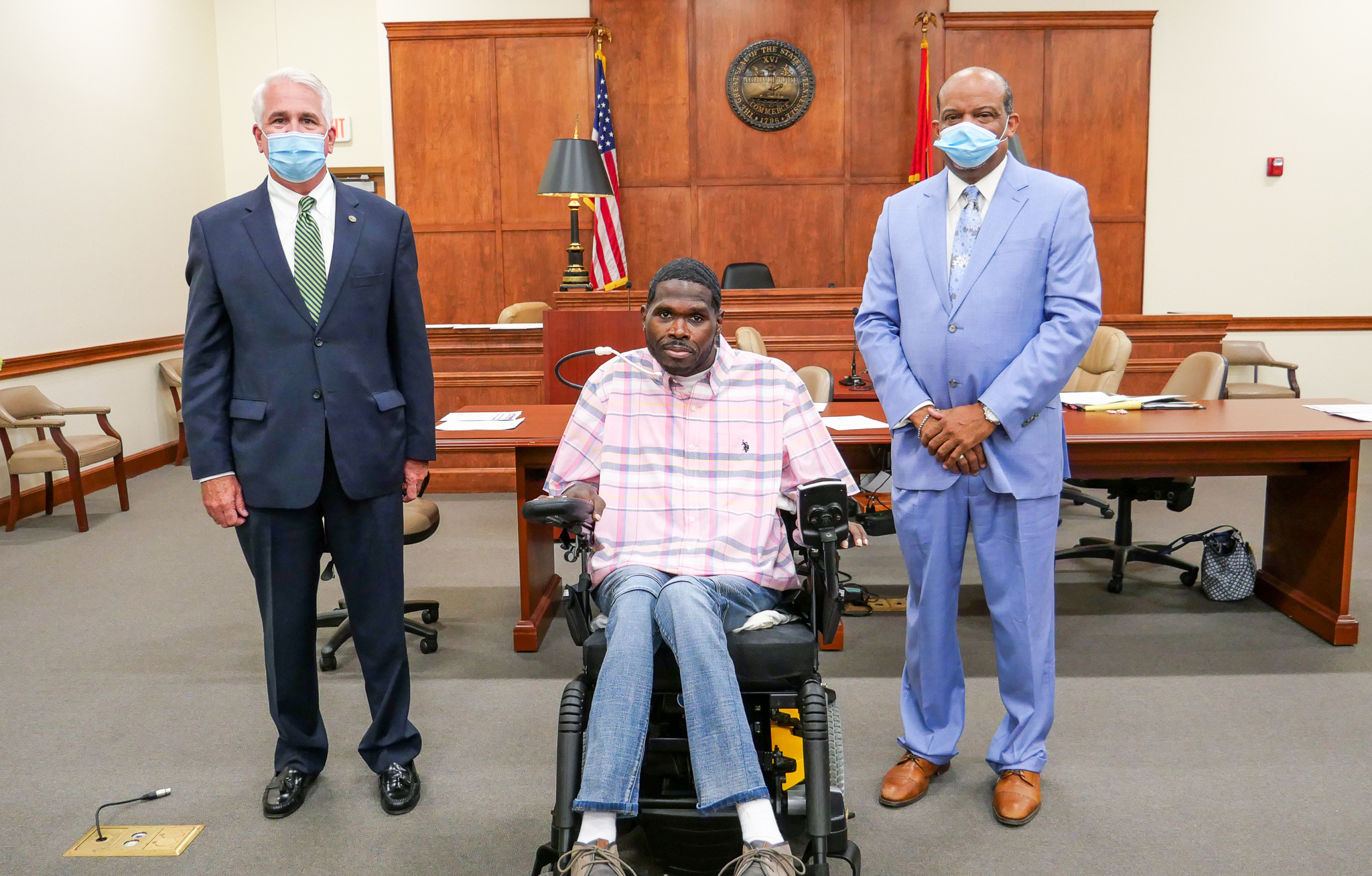 Three men in court room two standing one in wheelchair